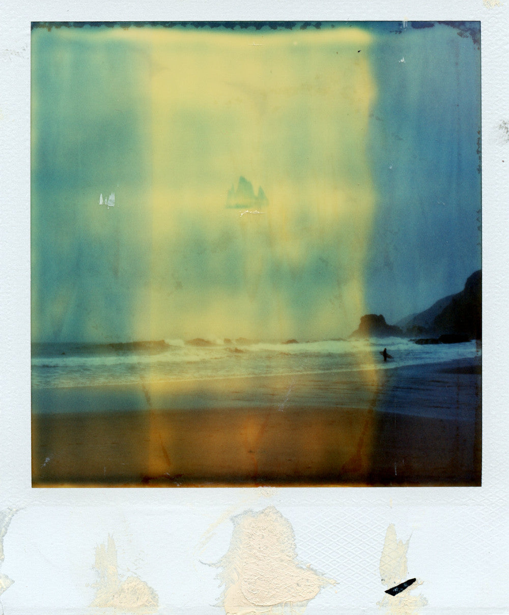 Polaroid of a surfer on a stormy day at St AGnes