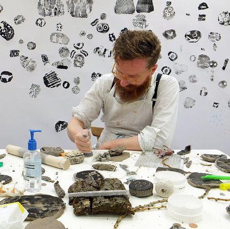 Artist and illustrator Stephen Fowler in his studio, in the process of creating stamps with a spread of tools and materials in front of him.