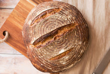 Load image into Gallery viewer, Round sourdough loaf bread on a wooden cutting board.