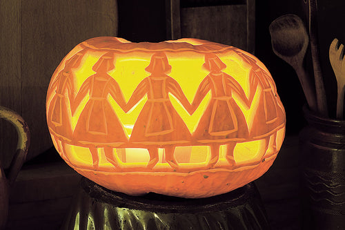 Pumpkin carved with maidens in a hand, holding hands.
