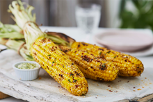 Load image into Gallery viewer, Beautifully photographed grilled corn on the cob, placed on a light grey board along with a dip.