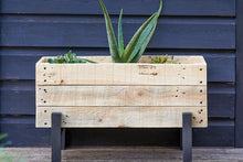 Load image into Gallery viewer, A wooden planter box with contrasting legs featuring succulents and placed against a wooden navy background.