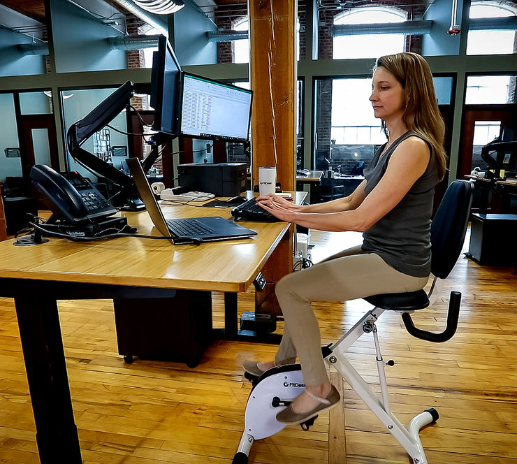 Woman Riding FitDesk Standing Desk Bike in office