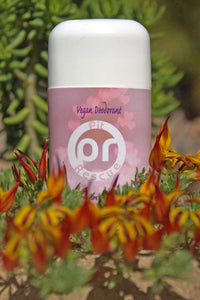 "white deodorant tube with a variegated pink background and a white circle with white letters ""P"" and ""R"" inside the circle, the white letters are abbreviation for pit rescue, deodorant tube is partially hidden by blooming parrot's beak in orange and red"