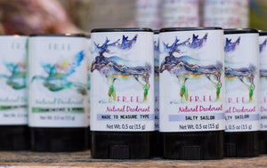 black deodorant tube with white label showing a moose that is made from a mountain scene, more black deodorant tubes with white labels showing dove with wings spread, green or blue band at bottom of label with fragrance description, dove is mostly blue and made from a nature scene of the sun setting over a meadow scene