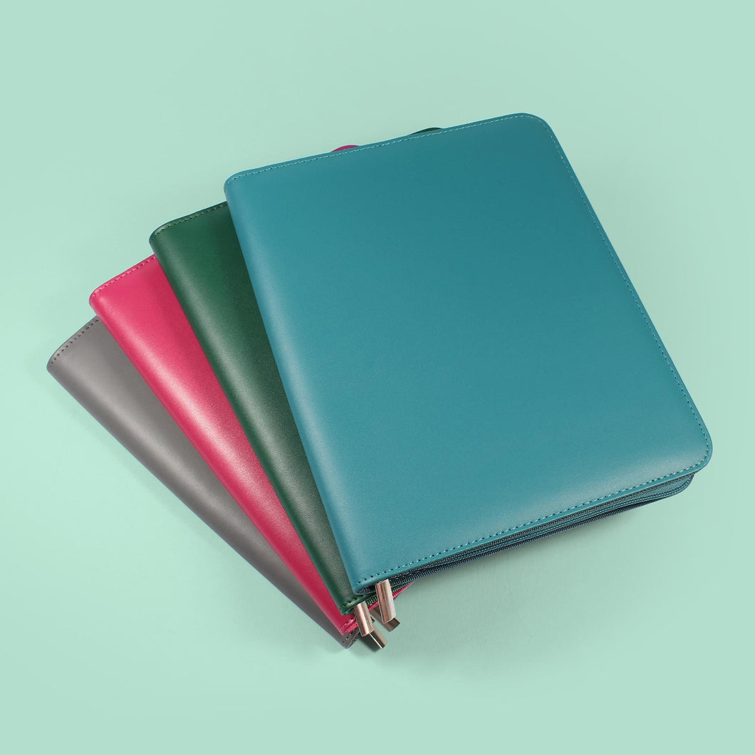 Collection of blue, green, grey and pink diary covers stacked and fanned out
