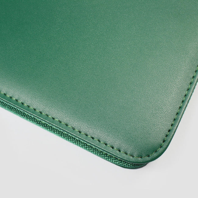 Corner and close up of stitching on a dark ivy green diary cover
