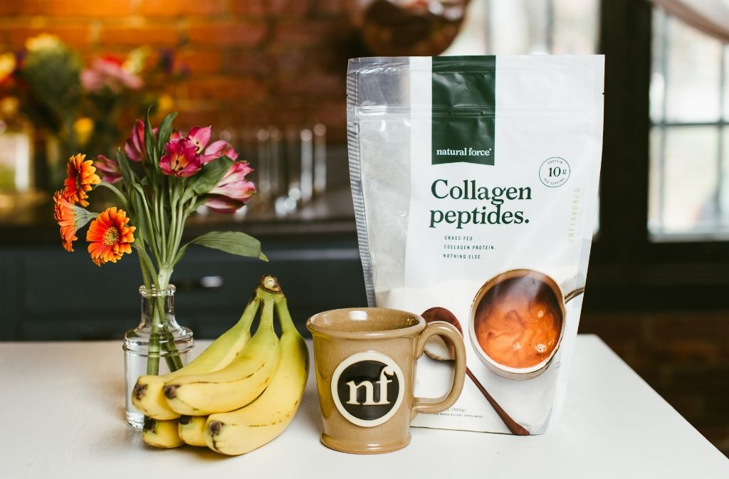 a handmade natural force mug containing coffee with collagen peptides on a counter beside a bag of natural force collagen peptides and bananas