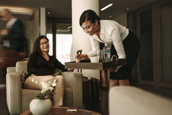 Airport lounge waitress serving coffee to female passenger