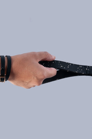 hand holding a black rubber dog lead by the handle