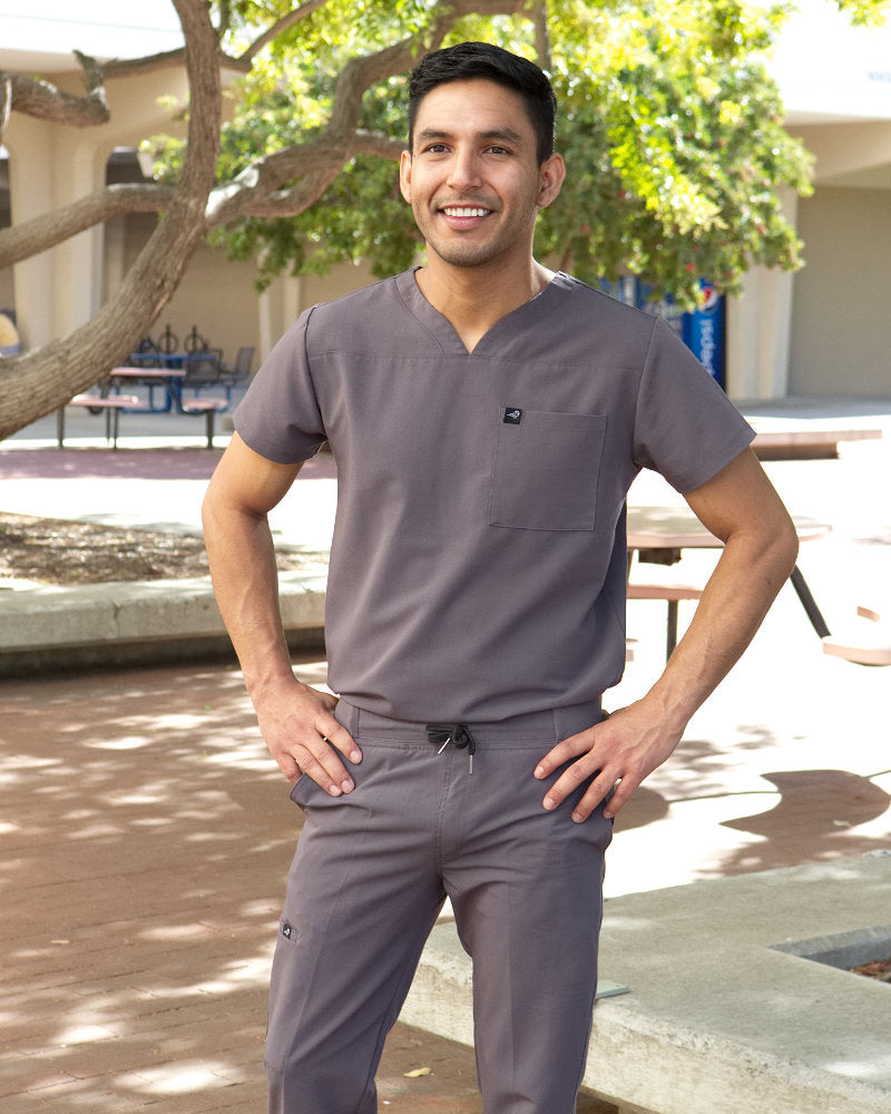 Black Finch Streamline Top.  Modern Athletic fit V-neck Men's  medical scrubs top in gray, lifestyle view with models face.