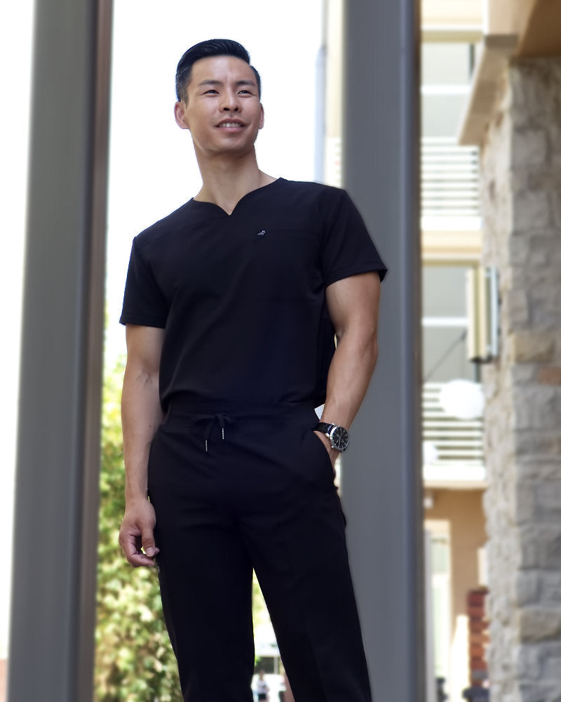 Black Finch Streamline Top.  Modern Athletic fit V-neck Men's scrub top in black, lifestyle view with models face.