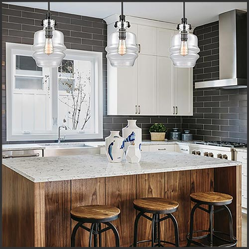 A kitchen with white cabinets, dark grey subway backsplash tile, and an island with a marbled countertop and wooden siding and stools.