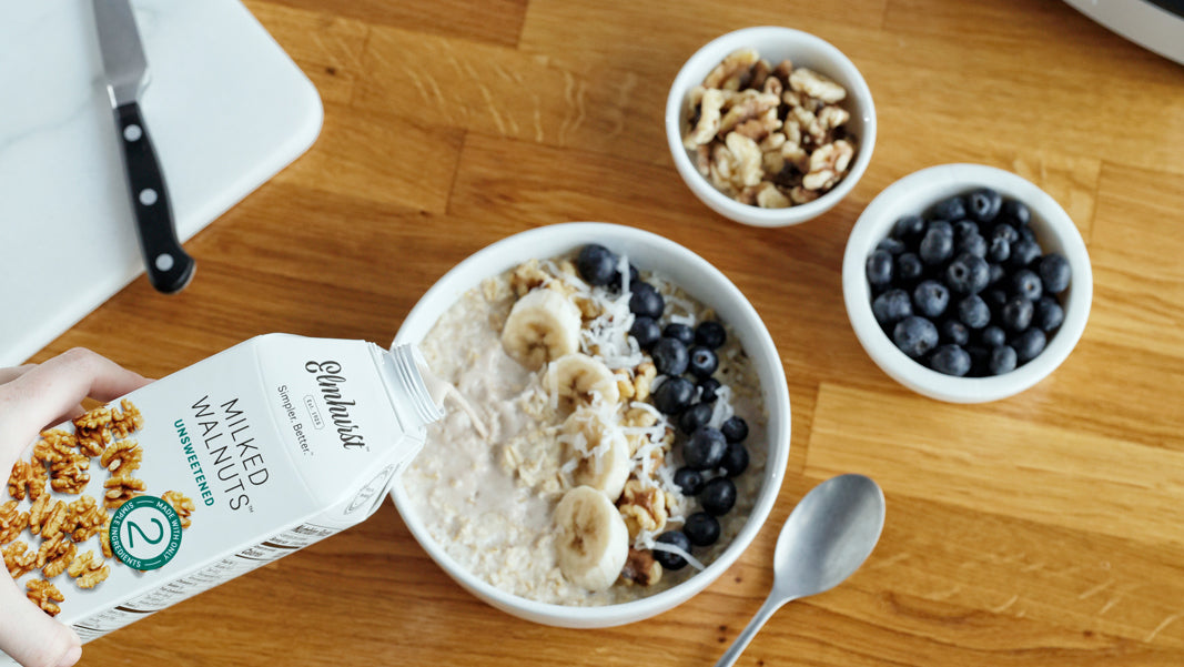 a bowl of oats, walnuts and blueberries with Elmhurst Walnut Milk