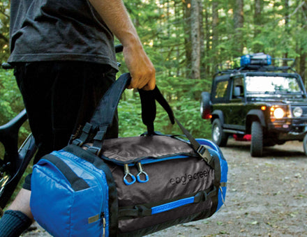 Featuring the cargo hauler duffel from Eagle Creek. A man carrying a blue and black duffel is returning to his jeep in the middle of a forest.