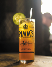 Load image into Gallery viewer, Pimm's Cup shown on table full of famous Pimm's cocktail and a wedge of lime.
