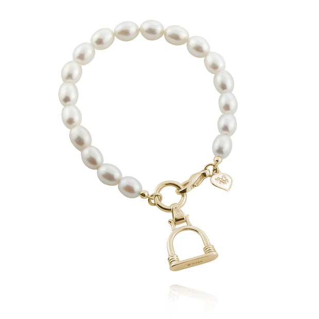 designer solid gold stirrup and cultured pearl bracelet on a white background.