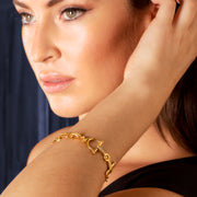 Model wearing Designer 9ct solid gold and 24 diamond horsebit  bracelet on purple backdrop.