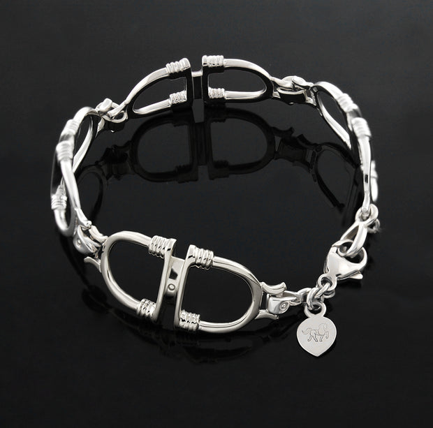 designer solid silver stirrup and leather strap bracelet on black background