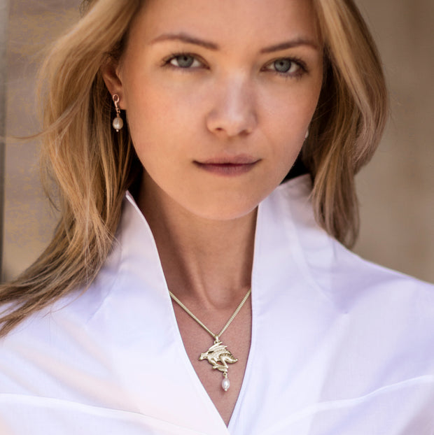 model wearing gold carved hare with pearl drop Designer necklace