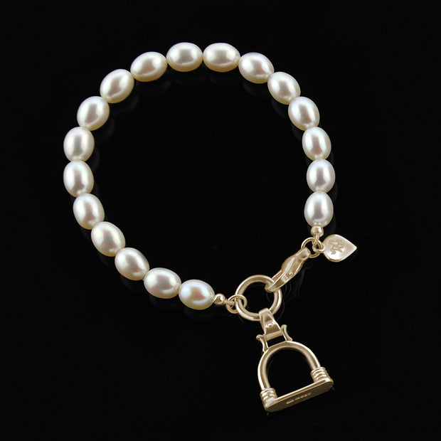 designer solid gold stirrup and cultured pearl bracelet on a black background.