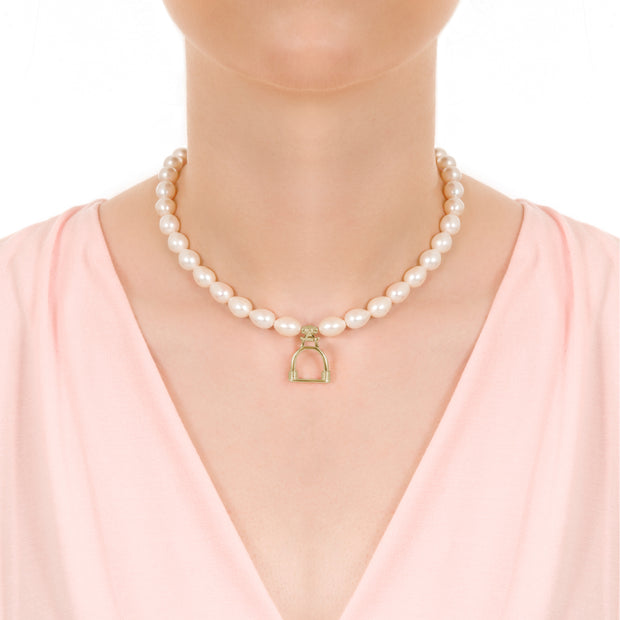 Close up shot of model wearing Designer solid 9ct gold vintage stirrup and cultured pearl necklace on white background