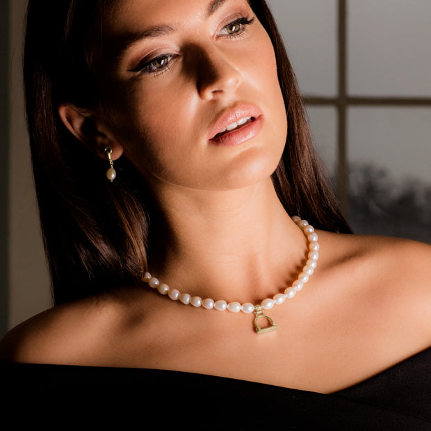Model wearing Designer solid 9ct gold vintage stirrup and cultured pearl necklace.