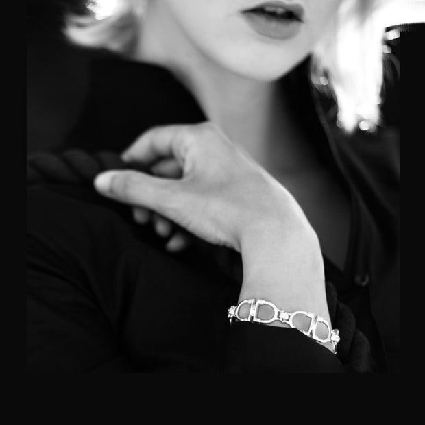 model wearing designer solid silver stirrup and leather strap bracelet Black and white image