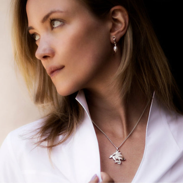 model wearing designer silver carved hare necklace