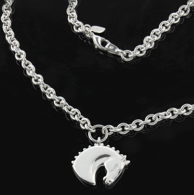 Designer solid silver carved horsehead necklace on heavy chain on black background.