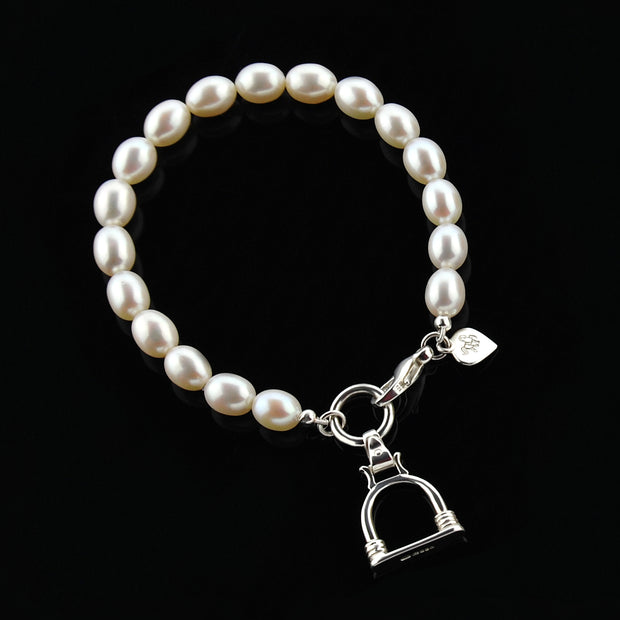 designer silver and cultured pearl bracelet with vintage stirrup charm on black.