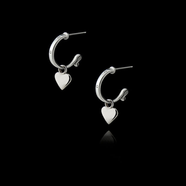 designer solid silver leather strap hoops with removable heart drop earrings on black background.