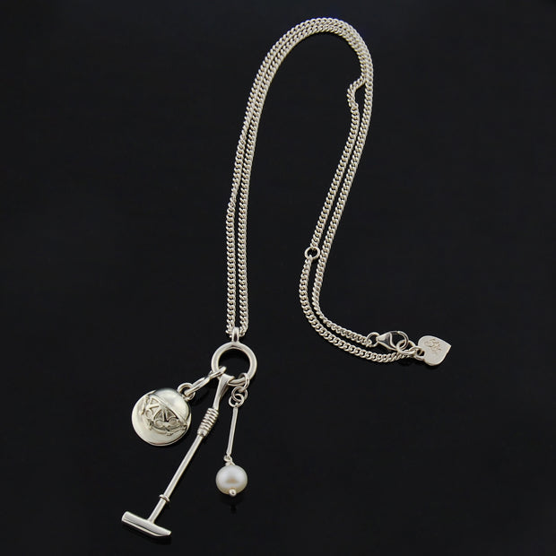Designer Solid silver and cultured pearl polo necklace with mallet helmet and ball on black background.