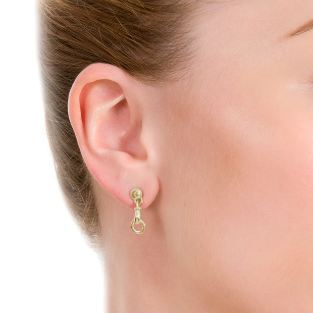 close up image of model wearing designer solid 9ct yellow gold horse bit inspired drop earrings on white background.