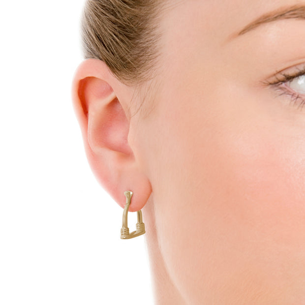 close up shot of model wearing designer 9ct gold vintage stirrup inspired hoop Badminton earrings.