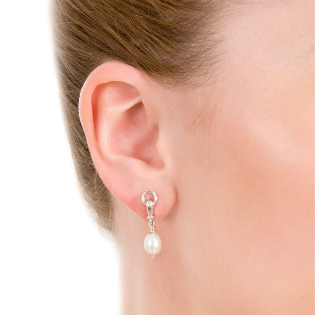 close up of model wearing designer solid silver and cultured pearl ascot drop earring on white background.