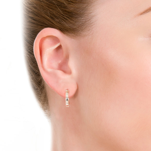 earshot of model wearing designer solid silver leather strap hoop earrings on white background