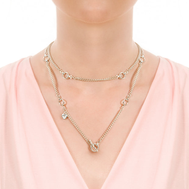 Close up of model wearing designer solid silver link and curb chain necklace with silver leather strap details and ring and toggle catch.