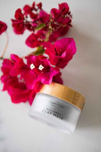 Samudra Skin & Sea Clay Mask, bottle beside flowers