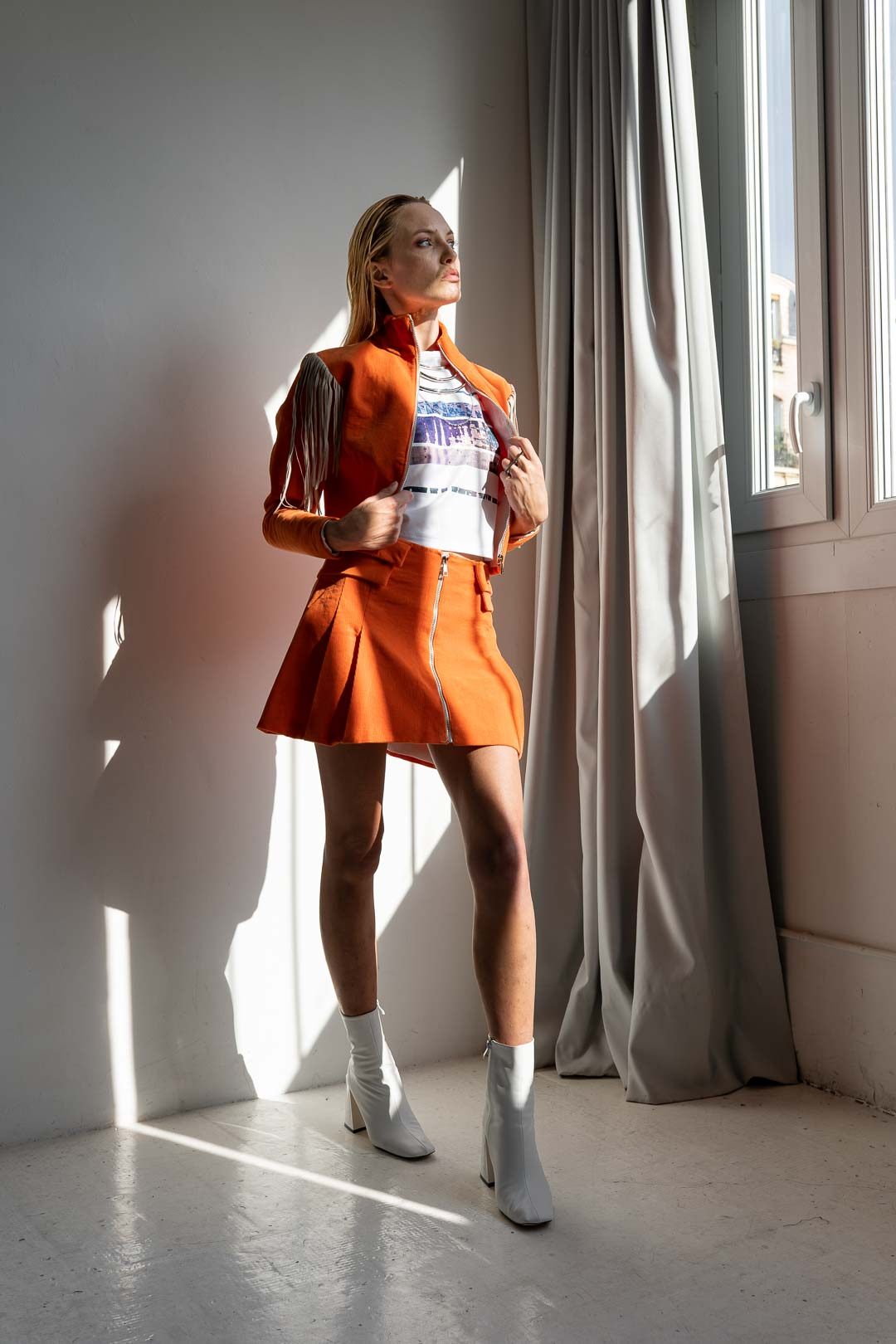 female model in orange outfit during a fashion shoot