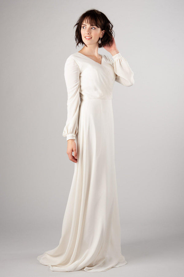 Modest wedding dress with long sleeves that flow around the around, dainty v-neck, with a slight train. Found at LatterDayBride, a salt lake city bridal shop.