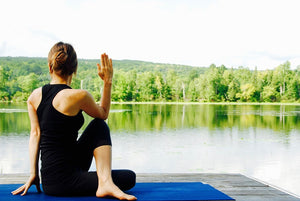 Lady performing seated spinal twist yoga pose beside a lake