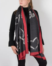 an image showing a grey cashmere mix scarf with a red heart print