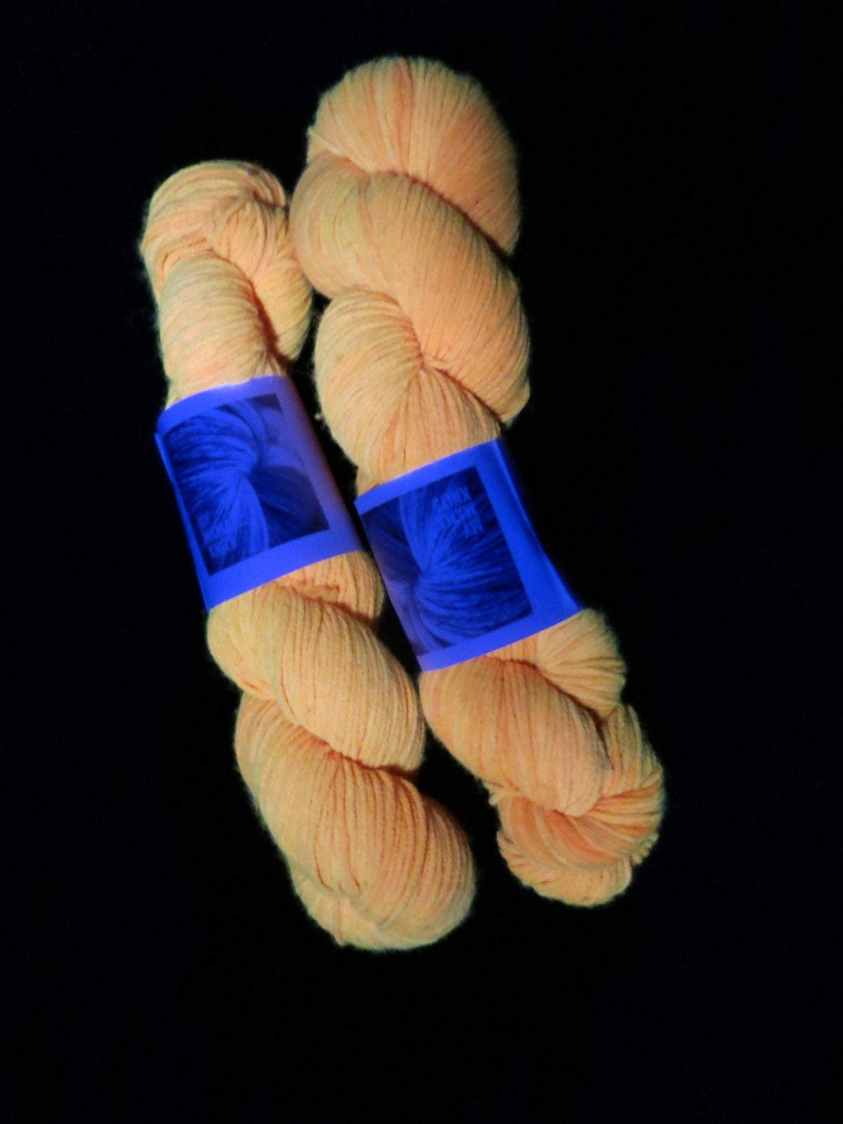 uv reactive orange yarn fluorescing under blacklight