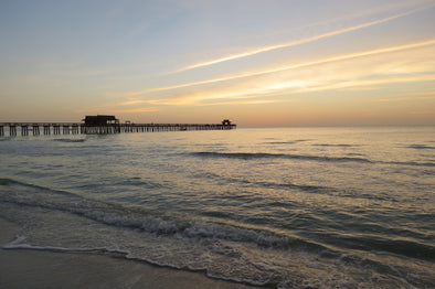 sun setting on the naples pier and gulf of mexico