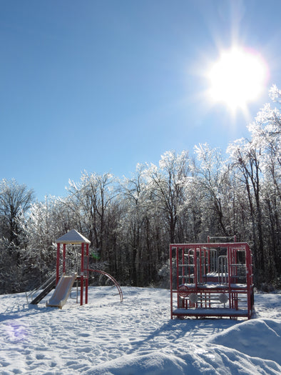 ice covered playground and bright, sunny, blue skies on a winter's day