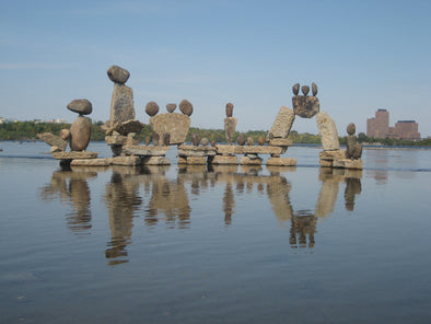 rocks balancing on one another to create a free-standing structure in the ottawa river
