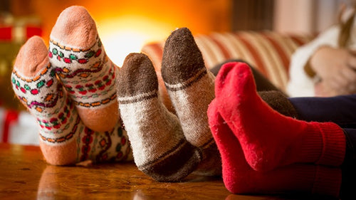Three pairs of feet warm by a fire. Join our Rock the Socks Drive to donate socks to residents of our affordable housing communities.