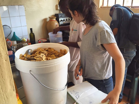 woman and bucket of plantain chips inside processing facility