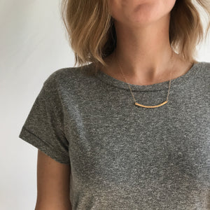Minimal Gold Bar Necklace. This curved hammered bar necklace is hand-crafted by Erin Bess in Indiana. The minimalist style necklace necklace will quickly be the one you reach for everyday. The simple hammered bar necklace adds the perfect amount of sparkle to everyday outfits.